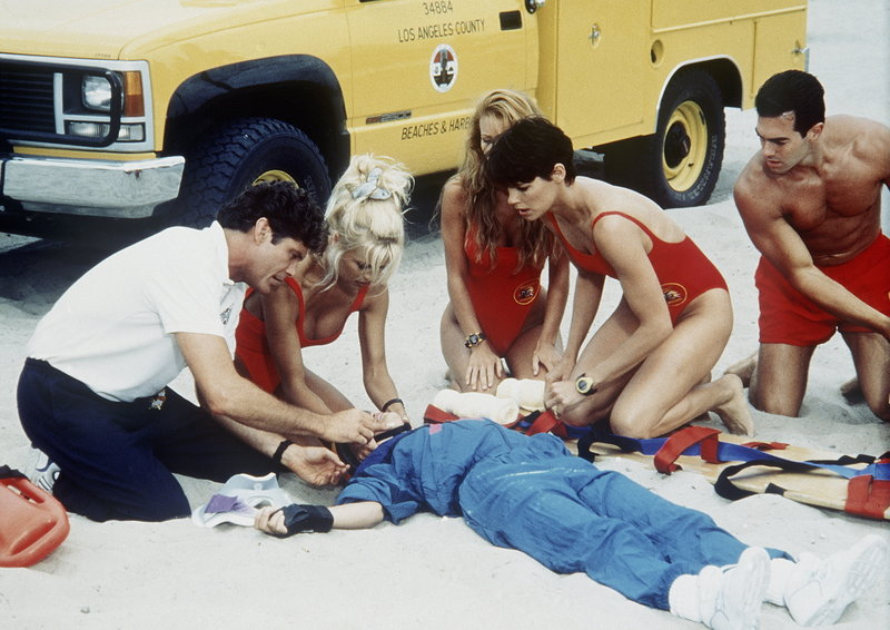 Das gesamte Baywatch-Team bemüht sich um einen Verunglückten am Strand. – Bild: Puls 4