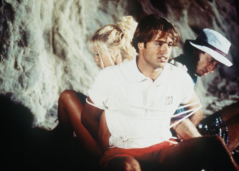 Gangster haben C. J. (Pamela Anderson), Basel (Alan Altshuld, r.) und Matt (David Charvet, M.) in der Höhle gefesselt. – Bild: Puls 4