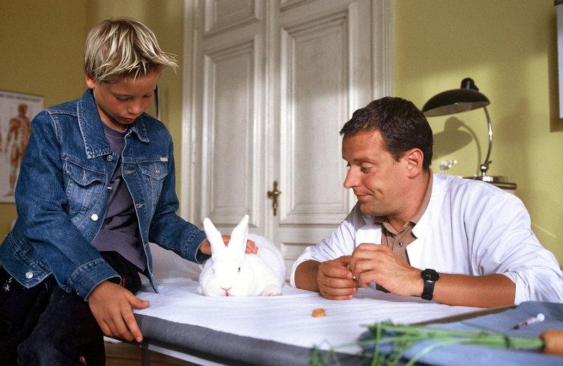 Weil der Tierarzt geschlossen hat, bringt Kevin (Kevin Brandt, l.) sein krankes Kaninchen zu Dr. Brotesser (Wolfgang Wagner, r.) in die Praxis. – Bild: Puls 8
