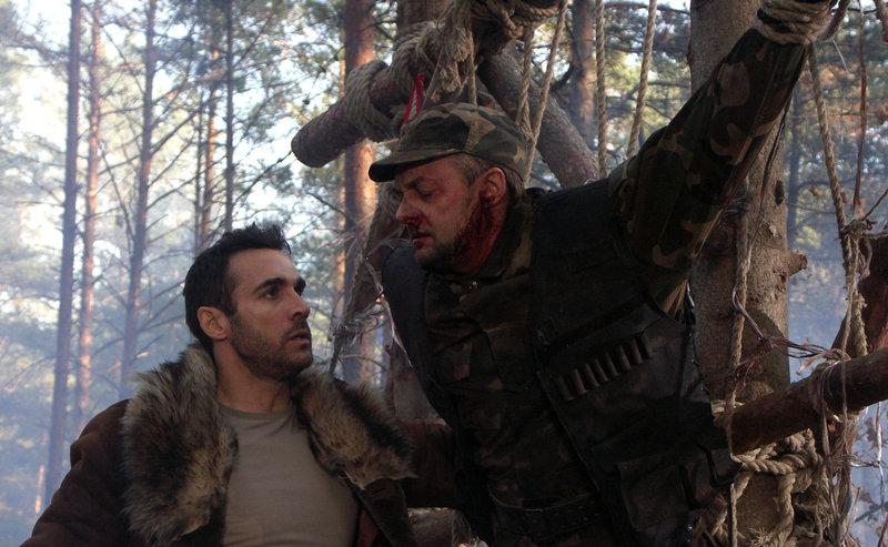 Als Duncan (Adrian Paul, l.) den gefesselten und misshandelten Sicherheitsbediensteten (Sakalas Uzdavinys, r.) im Wald findet, ist ihm klar, er kommt der Quelle der Unsterblichkeit immer näher ... – Bild: Puls 8