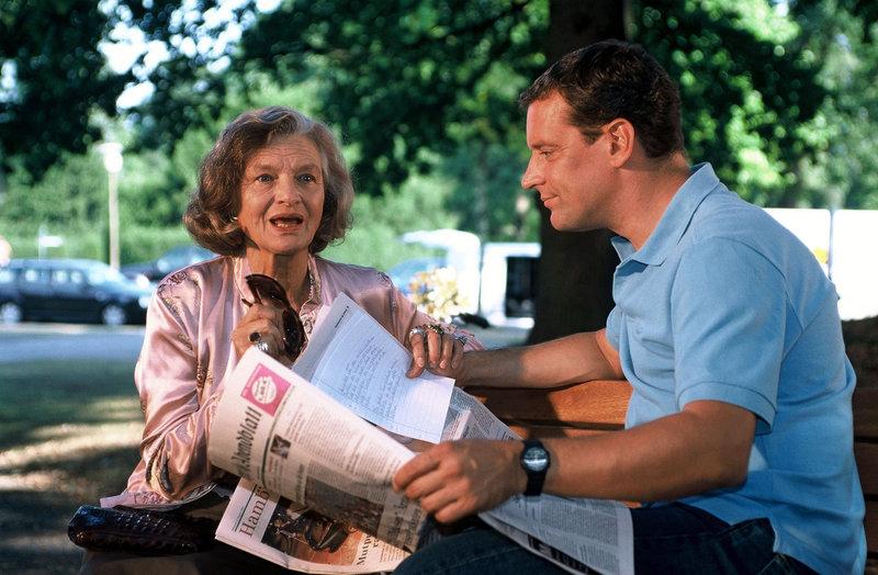 Broti (Wolfgang Wagner, r.) liest der blinden Charlotte (Brigitte Antonius, l.) selbst erdachte gute Nachrichten aus der Zeitung vor. – Bild: Puls 8