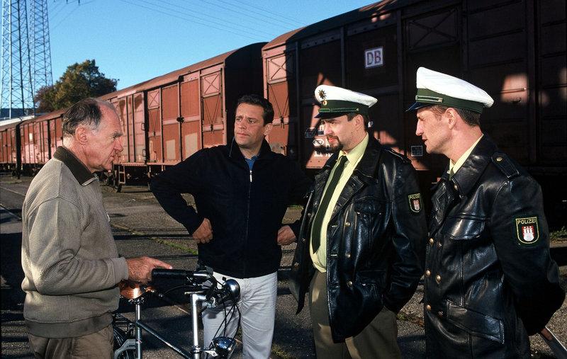 Broti (Wolfgang Wagner, 2.v.l.) wurde das Fahrrad gestohlen. Düwel (Carl Heinz Choinski, l.) behauptet aber, dass das fahrrad ihm gehöhrt. Die Polizisten Hartmut (Alexander Hörbe, 2.v.r.) und Lutz (Tim Wilde, r.) sind ratlos. – Bild: Puls 8