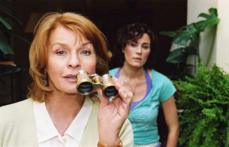 Die neugierige Helga (Senta Berger, l.) traut ihrem charmanten wie attraktiven Nachbarn Cem nicht und greift zum Opernglas... – Bild: Puls 8