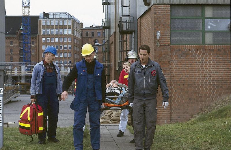Paul Karmann, der Baustellenleiter, wird mit einem Herzinfarkt von den Rettungsfliegern abtransportiert. (v.l.n.r. Klaus Peeck, Oliver Warsitz, Bruno Apitz, n.n., Marlene Marlow, Patrick Wolff) – Bild: ZDF
