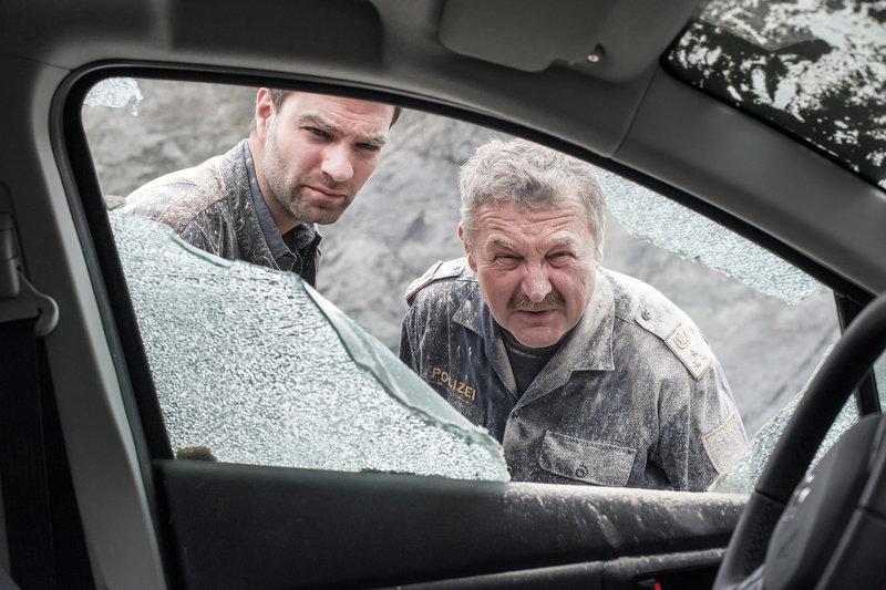 Nach der Explosion - Lukas Roither (Jakob Seeböck, l.) und Kroisleitner (Ferry Öllinger, r.) schauen die Verwüstungen an. – Bild: ZDF