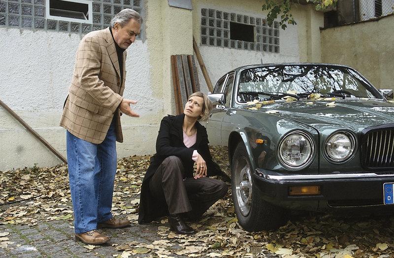 Grindemann (Niolas Lansky) versucht Susanne v. Hagenberg (Christine Döring) klar zu machen, dass sie an seinem Wagen keine Spuren finden wird. – Bild: ZDF