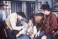 Ben Cartwright (Lorne Greene, 2.v.l.) versucht, die Wahrheit aus dem Zeugen Dixie (Malcolm Atterbury, 2.v.r.) herauszupressen, der Adam schwer belastet. – Bild: Paramount Pictures