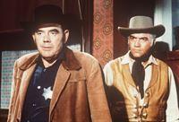 Ben Cartwright (Lorne Greene, r.) versucht, den Sheriff (James Westerfield, l.) zu beschwichtigen, dessen aufsässiger Sohn zu den Viehtreibern gehört, die die Stadt unsicher machen. – Bild: Paramount Pictures