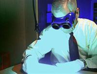 Ron Depaco beweist durch die Lasertechnik, dass der Fingerabdruck auf der Postkarte von Valerian Trifa ist. – © RTL Nitro