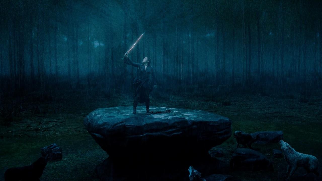 Nimue (Katherine Langford) weist mit Excalibur die CGI-Wölfe in die Schranken. Netflix