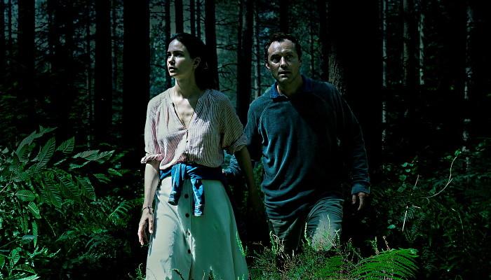 """Platz 2: """"The Third Day"""" (HBO/Sky): Schon das Setting sorgt für ein mulmiges Gefühl: """"The Third Day"""" spielt auf der real existierenden Insel Osea, die nur über einen schmalen, lediglich bei Ebbe passierbaren Schotterweg erreichbar ist. Eben hierhin verschlägt es den von Jude Law (""""The New Pope"""") in einer Tour-de-Force-Performance verkörperten Sam, nachdem er eine junge Frau vor dem Selbstmord bewahrt hat. Während die Episoden eins bis drei seine Konfrontationen mit den Insulanern schildern, die archaische Bräuche pflegen, schlägt sich in den Folgen vier bis sechs die von Naomie Harris (""""Moonlight"""") dargestellte Helen mit den unheimlichen Bewohnern herum. Dass die beiden """"Sommer"""" und """"Winter"""" betitelten, zeitlich voneinander getrennten Stränge in einer Verbindung stehen, liegt auf der Hand. Die grauenhaften Dimensionen der Beziehung offenbaren sich allerdings erst nach und nach. Kenner des britischen Schauerkinos dürfte die Miniserie unweigerlich an """"The Wicker Man"""", den Klassiker des Folklorehorrors, erinnern. Ein billiger Abklatsch ist """"The Third Day"""" aber mitnichten. Vielmehr entspinnt sich vor unseren Augen eine atmosphärisch ungemein dichte Mischung aus Psychothriller und Drama, die bestürzend eindringlich von Verlust, Trauer, Schuld und familiärer Verantwortung erzählt. Formal sticht der Jude-Law-Abschnitt hervor, der durch Unschärfe, seltsame Kamerawinkel, eigenartige Farbspiele, extreme Nahaufnahmen und ein experimentelles Sounddesign eine komplett aus den Fugen geratene Welt heraufbeschwört. Sams Erleben kommt einem Abstieg in die Hölle gleich. Die Harris-Passage ist deutlich klassischer gefilmt, deshalb aber nicht weniger spannend. Neben den Sommer- und Winter-Teilen gibt es auch ein zwischengeschaltetes, """"Herbst"""" genanntes Kapitel, das als zwölfstündiges, in einer einzigen Einstellung gedrehtes Live-Event ausgestrahlt wurde. Für das Verständnis der Serie ist dieses Mittelstück nicht notwendig. Als innovatives, den Inselschauplatz noch genauer erforschendes"""